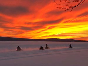 Snowmobilers riding into the sunset overRangeley Lake - Click on the image above to access more Maine winter images.